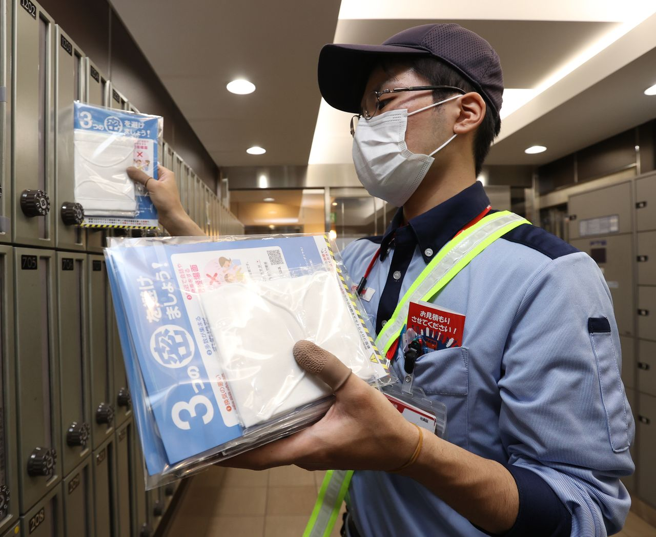 "A postal worker delivers  ""Abenomasks,"" cloth masks distributed by the government to every household in Japan, in Ōsaka on May 12. (© Jiji)"