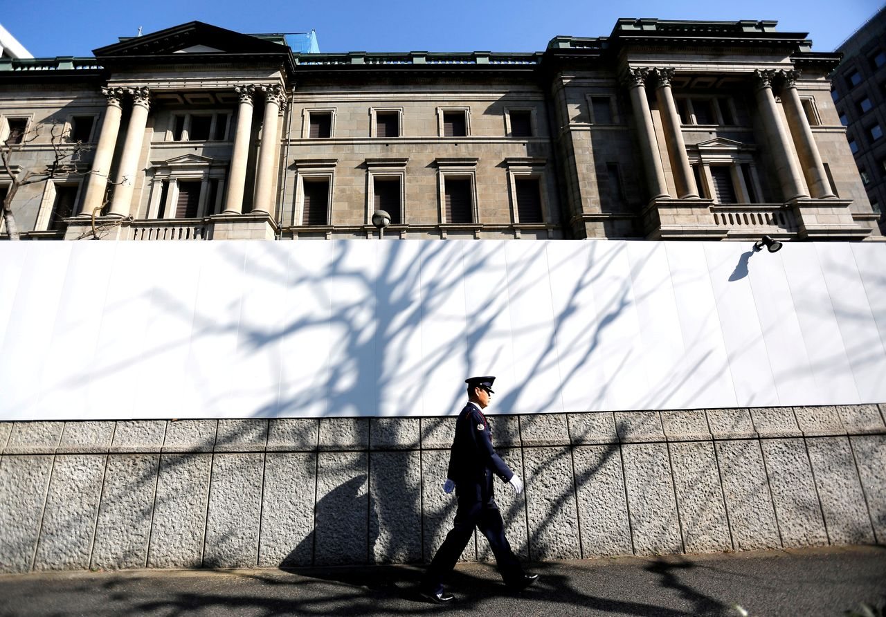FILE PHOTO: A security guard walks past in front of the Bank of Japan headquarters in Tokyo, Japan January 23, 2019. REUTERS/Issei Kato