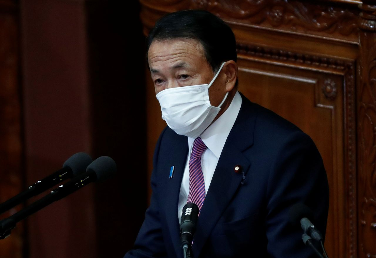 FILE PHOTO: Japan's Deputy Prime Minister and Finance Minister Taro Aso, wearing a protective face mask, delivers his policy speech at the opening of an ordinary session of the parliament in Tokyo, Japan January 18, 2021. REUTERS/Issei Kato