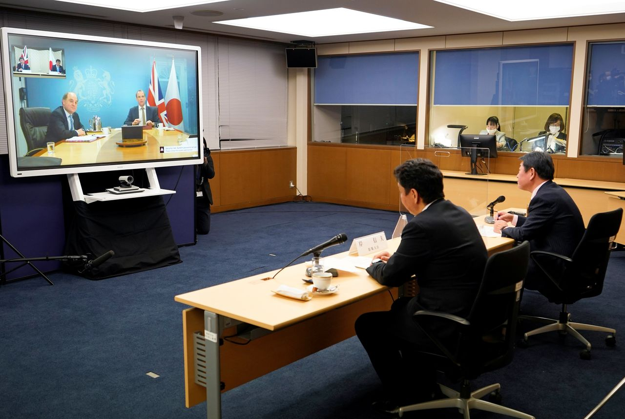 Japan's Defence Minister Nobuo Kishi and Foreign Minister Toshimitsu Motegi attend a video conference with Britain's Foreign Secretary Dominic Raab and Defence Minister Ben Wallace (on the screen) at the Foreign Ministry in Tokyo, Japan February 3, 2021. Franck Robichon/Pool via REUTERS