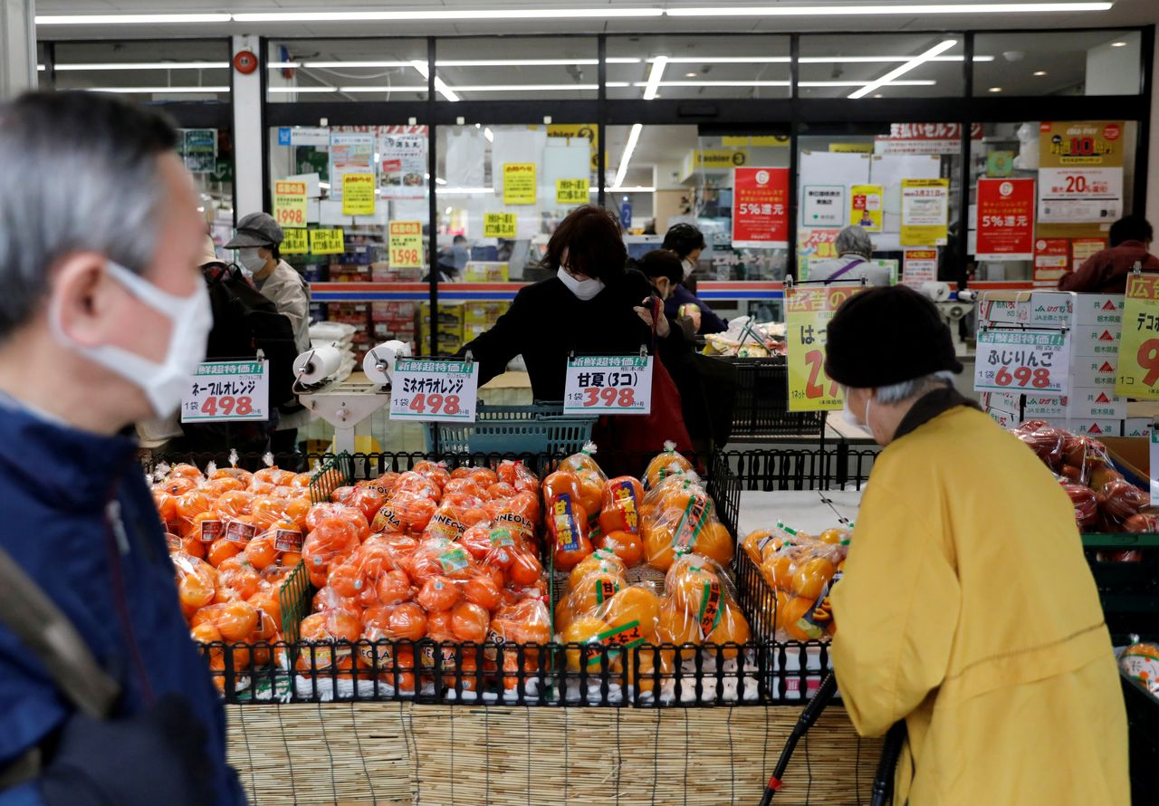 FILE PHOTO: Shoppers wearing protective face masks, following an outbreak of the coronavirus disease (COVID-19), are seen at a supermarket in Tokyo, Japan March 27, 2020. REUTERS/Issei Kato