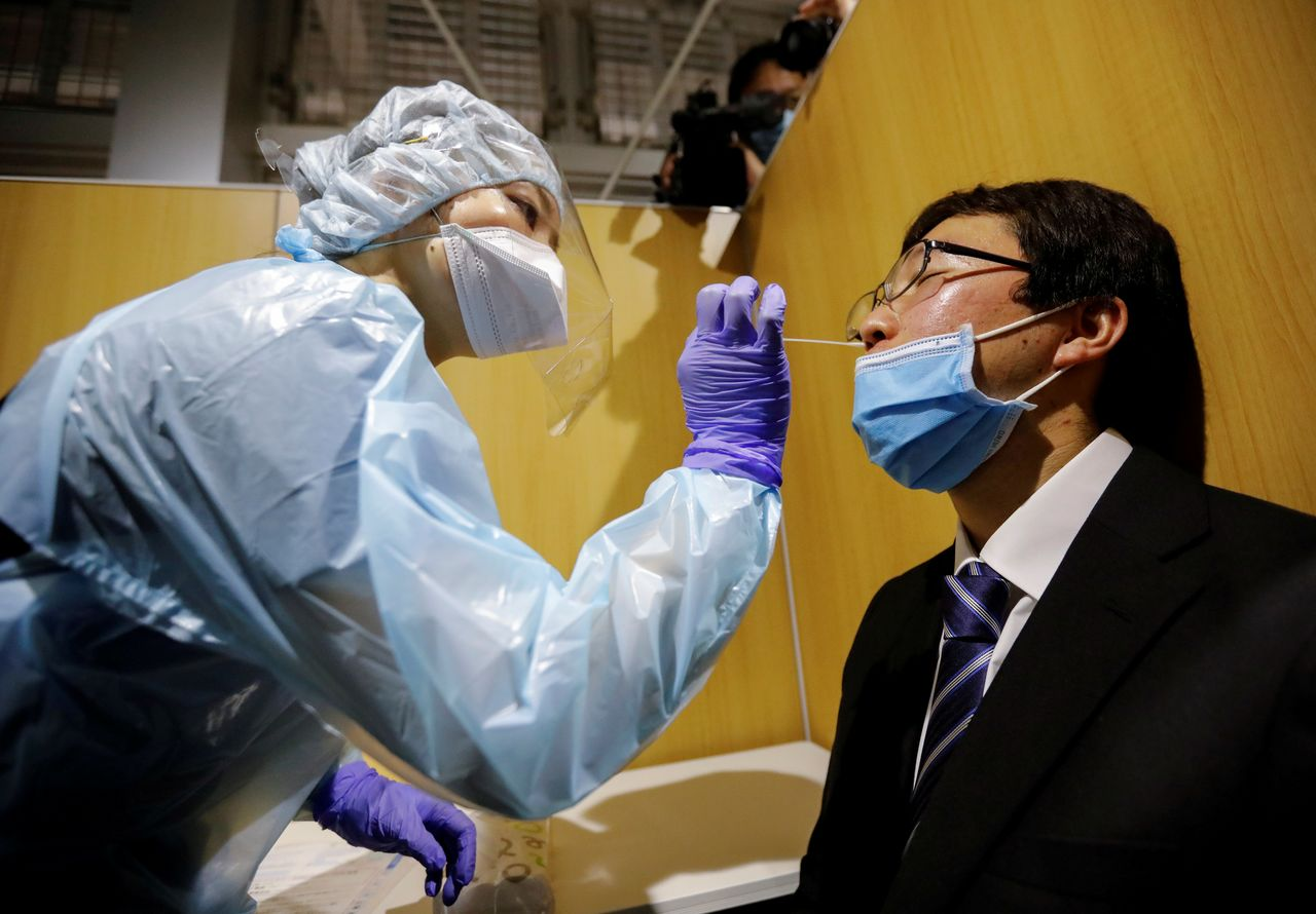 FILE PHOTO: A medical worker wearing a protective suit conducts a simulation for a polymerase chain reaction (PCR) test at the newly opened Narita International Airport PCR Center in Narita, east of Tokyo, Japan November 2, 2020. REUTERS/Issei Kato