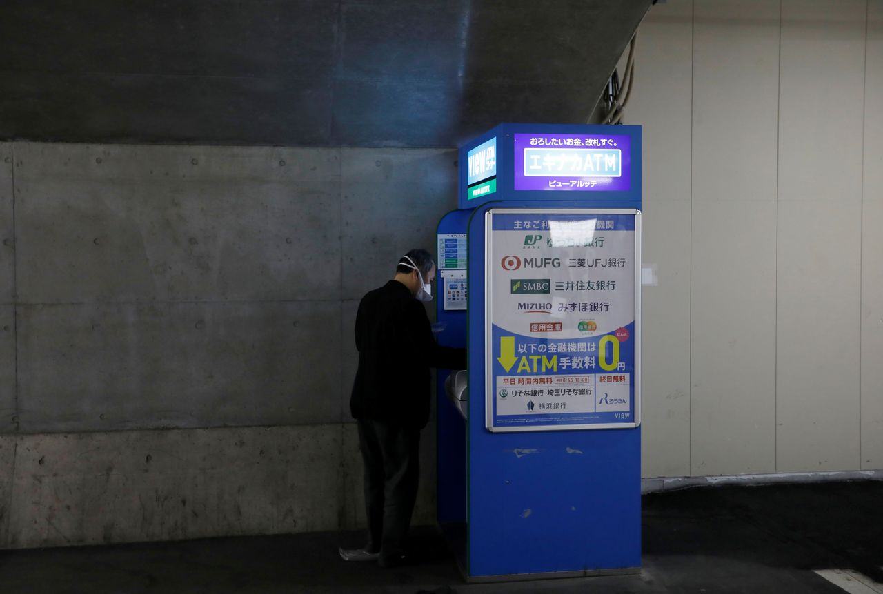 FILE PHOTO: A man wearing a protective mask, amid the coronavirus disease (COVID-19) outbreak, uses the ATM machine at a subway station in Tokyo, Japan, January 8, 2021. REUTERS/Kim Kyung-Hoon