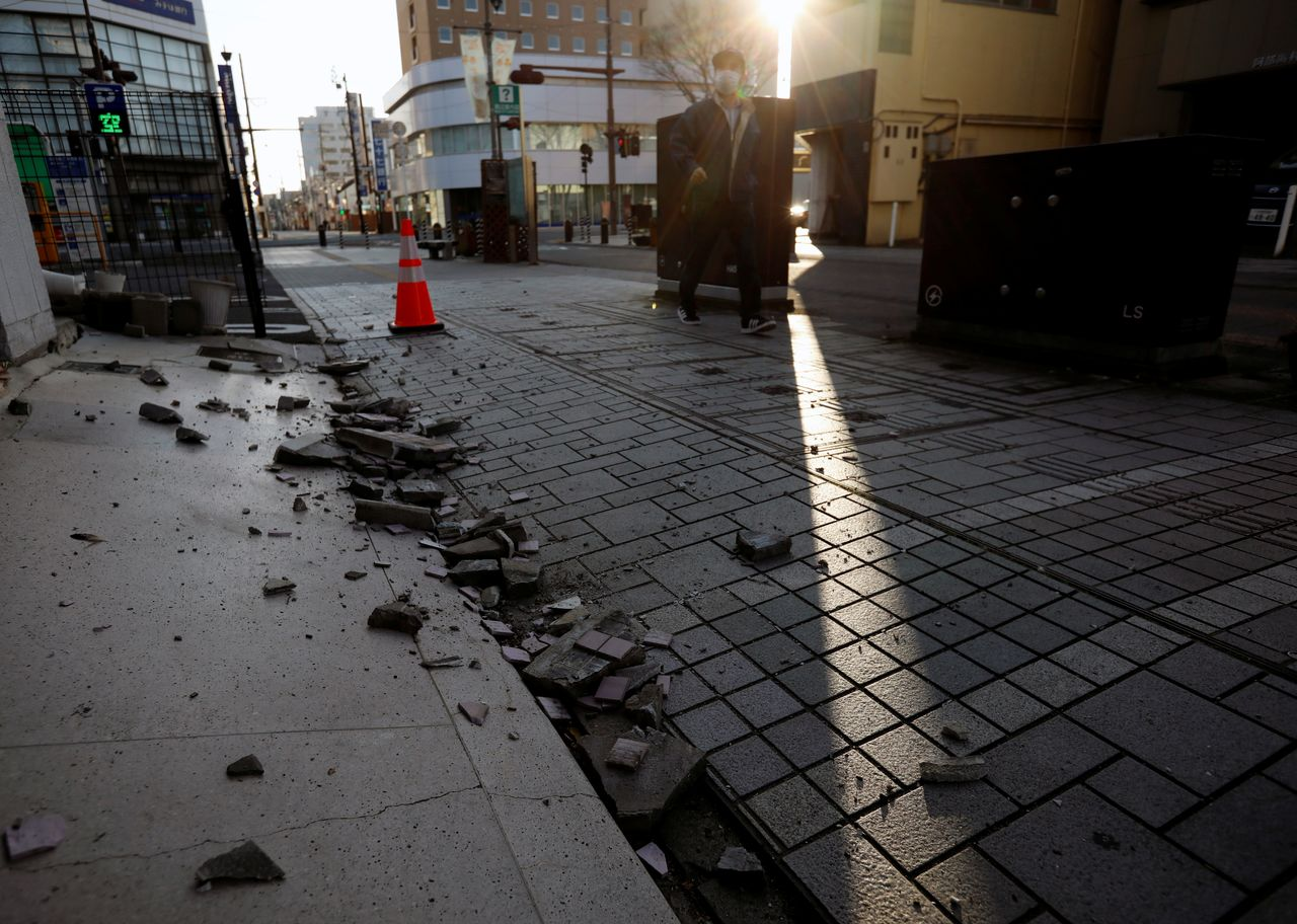 Collapsed exterior wall of a building caused by a strong earthquake are seen on the street in Iwaki, Fukushima prefecture, Japan February 14, 2021. REUTERS/Issei Kato