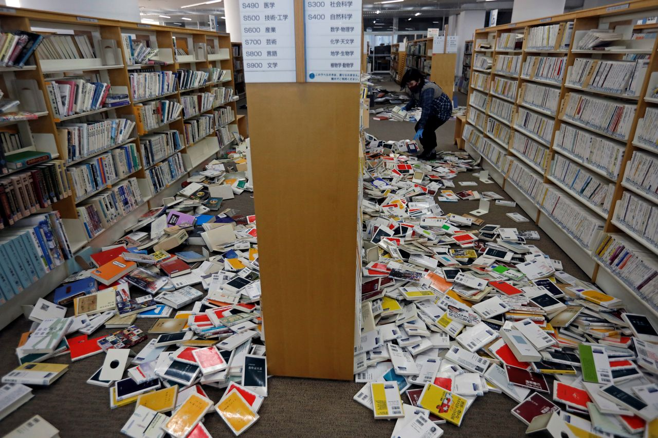A staff member of library tries to restore books after they fell from book shelves by a strong earthquake at Iwaki City library in Iwaki, Fukushima prefecture, Japan February 14, 2021. REUTERS/Issei Kato