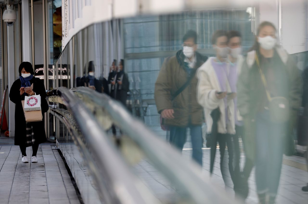 FILE PHOTO: Pedestrians wearing protective masks amid the coronavirus disease (COVID-19) outbreak, make their way in Tokyo, Japan, February 2, 2021. REUTERS/Kim Kyung-Hoon/File Photo