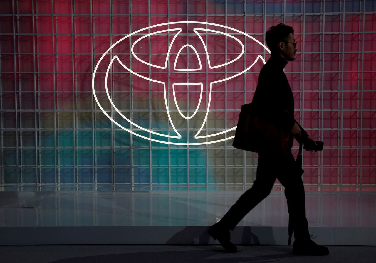 FILE PHOTO: A man walks past a Toyota logo at the Tokyo Motor Show, in Tokyo, Japan October 24, 2019. REUTERS/Edgar Su/File Photo