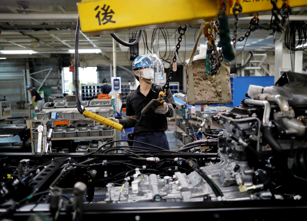 FILE PHOTO: An employee wearing a protective face mask and face guard works on the automobile assembly line at Kawasaki factory of Mitsubishi Fuso Truck and Bus Corp, owned by Germany-based Daimler AG, in Kawasaki, south of Tokyo, Japan May 18, 2020. REUTERS/Issei Kato