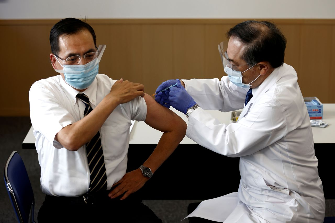 Director of the Tokyo Medical Center Kazuhiro Araki (L) receives a dose of the coronavirus disease (COVID-19) vaccine as the country launches its inoculation campaign, in Tokyo, Japan February 17, 2021. Behrouz Mehri/Pool via REUTERS