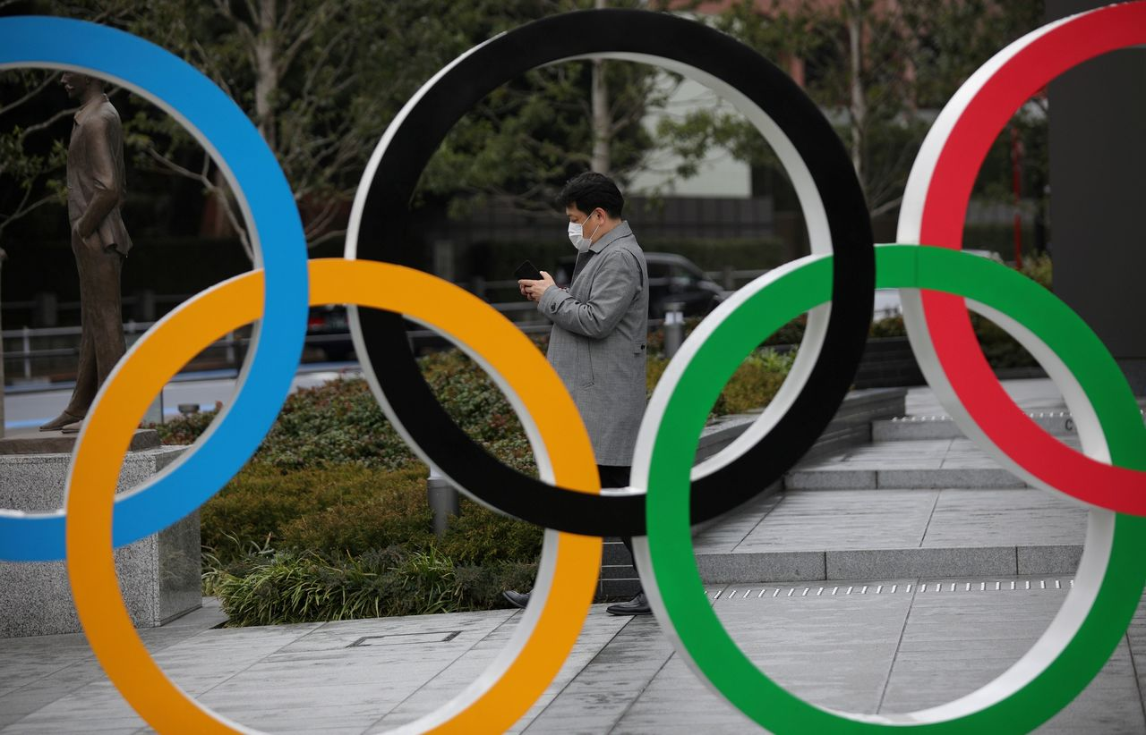 FILE PHOTO: A man looks at his mobile phone next to The Olympic rings in front of the Japan Olympics Museum in Tokyo, Japan, March 4, 2020. REUTERS/Stoyan Nenov/File Photo