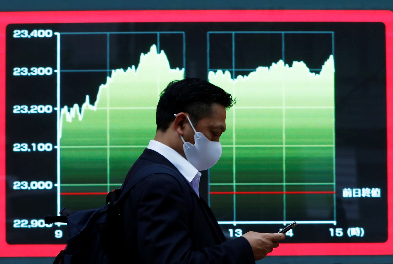 FILE PHOTO: A man wearing a protective face mask walks past a screen displaying a graph showing recent Nikkei share average outside a brokerage, amid the coronavirus disease (COVID-19) outbreak, in Tokyo, Japan November 2, 2020. REUTERS/Issei Kato/File Photo