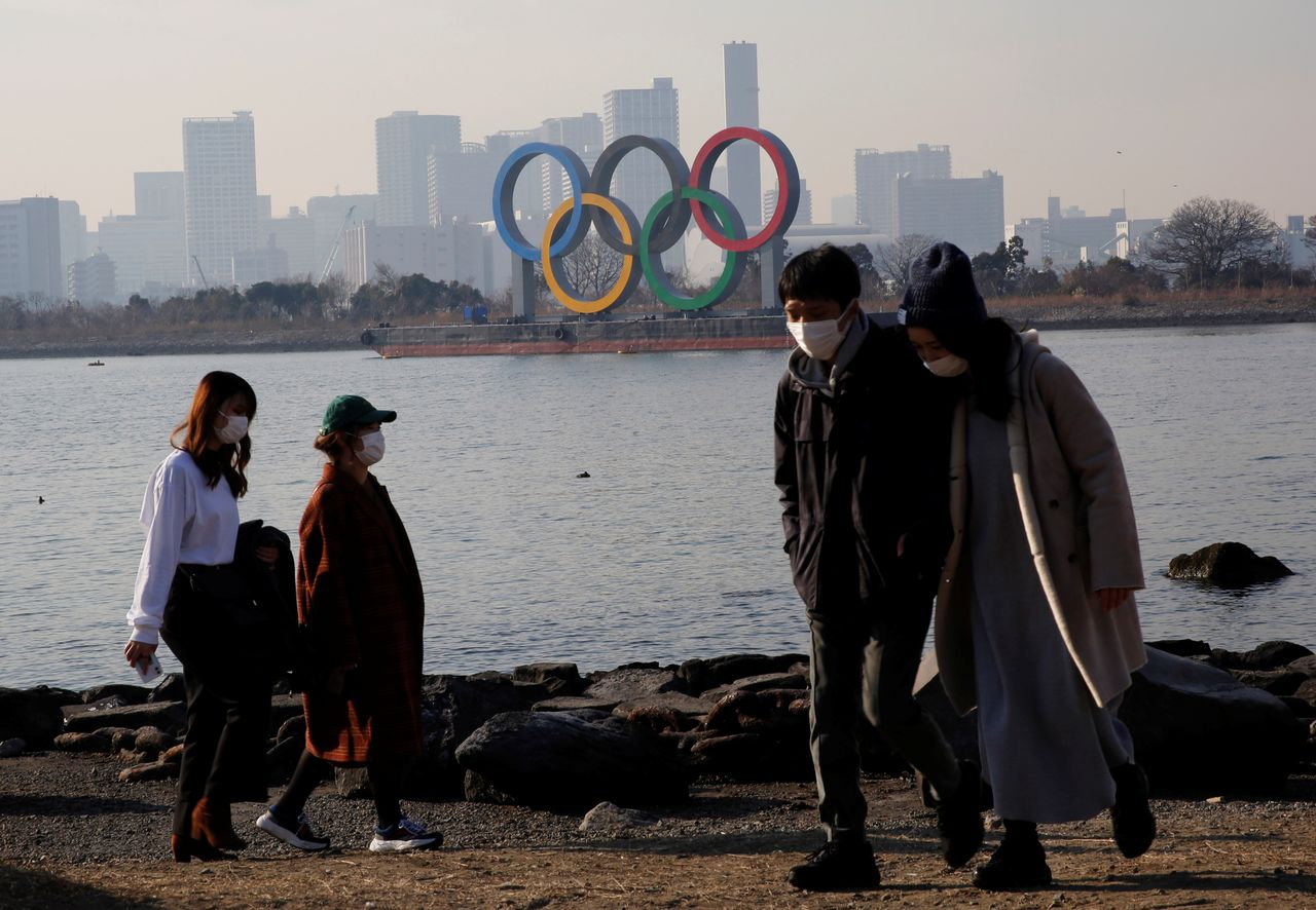 FILE PHOTO: People wearing protective masks, amid the coronavirus disease (COVID-19) outbreak, are seen in front of the giant Olympic rings in Tokyo, Japan, January 22, 2021. REUTERS/Kim Kyung-Hoon