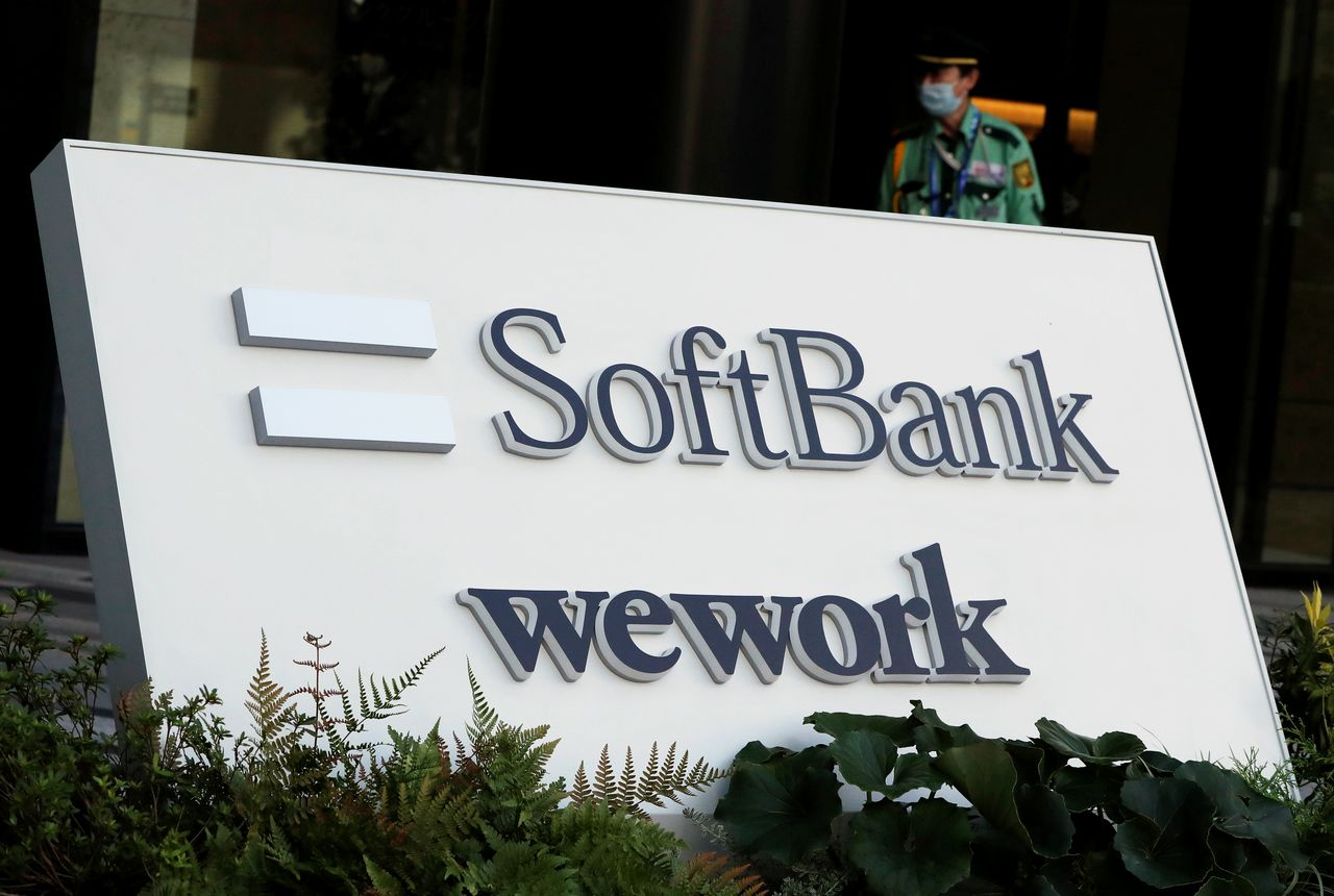 FILE PHOTO: The logos of SoftBank and WeWork are displayed in front of SoftBank's new headquarters building in Tokyo, Japan September 9, 2020. REUTERS/Issei Kato