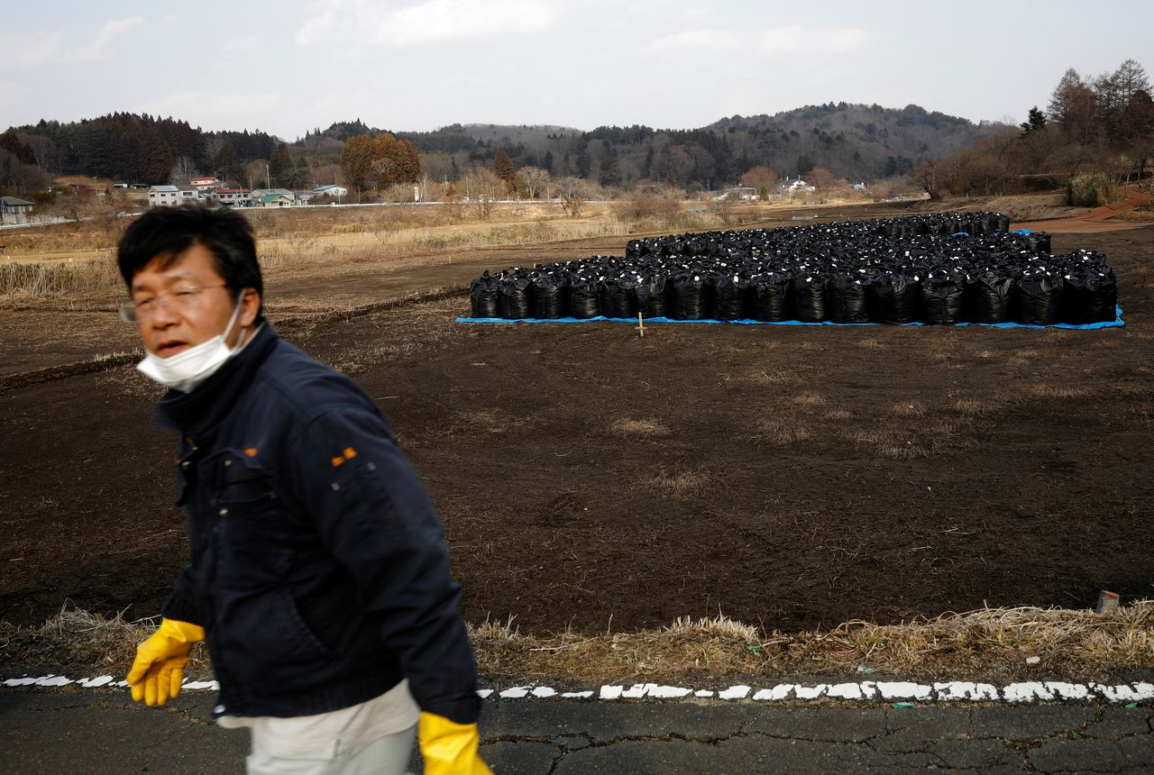 Sakae Kato walks past black bags containing contaminated soil from the fallout of the Fukushima nuclear plant, in a restricted zone in Namie, Fukushima Prefecture, Japan, February 21, 2021. Kato looks after 41 cats in his home and another empty building on his property. A decade ago, Kato stayed behind to rescue cats abandoned by neighbours who fled the radiation clouds belching from the nearby Fukushima nuclear plant. He won't leave. I don't want to leave, I like living in these mountains,