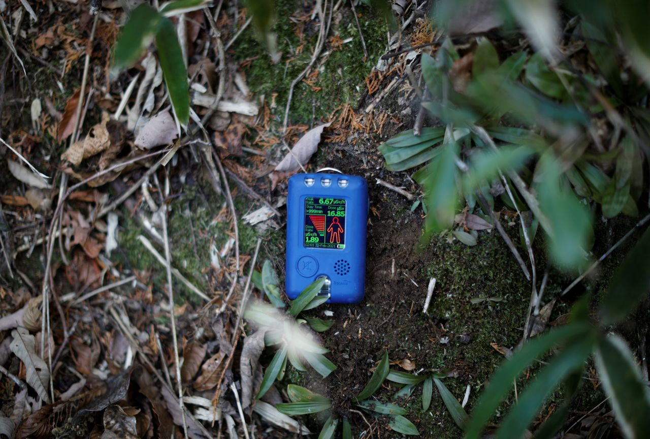 A radiation dosimeter, brought by a Reuters journalist, shows a reading of 1.89 microsievert per hour at Hisae Unuma's family graveyard, near her house that she lived in before being evacuated, as Unuma visits the graveyard on the anniversary of her husband's death in a restricted zone in Futaba, Fukushima prefecture, Japan, February 23, 2021. Unuma who's home where she lived, is 2.5 km away from the crippled Fukushima nuclear power plant, won't return even if the government scrapes the radioactive soil off her fields. Radiation levels around her house are around 20 times the background level in Tokyo, according to a dosimeter reading carried out by Reuters. Only the removal of Fukushima's radioactive cores will make her feel safe, a task that will take decades to complete. Never mind the threat from earthquakes, those reactors could blow if someone dropped a tool in the wrong place,