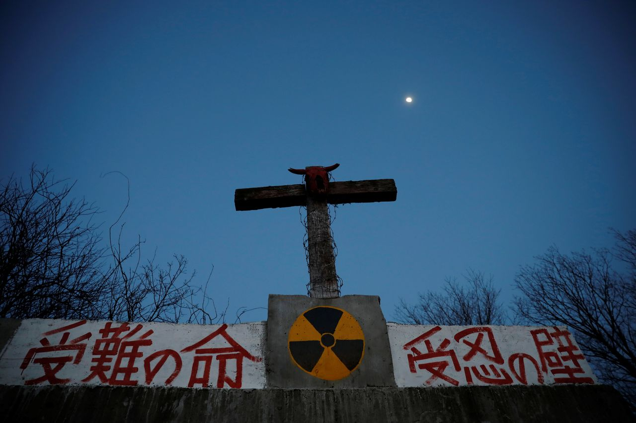 A bullocks's skull sits on top of a cross on a wall that bears a nuclear symbol, at the Ranch of Hope, a cattle farm owned by Masami Yoshizawa, who defied an order to cull his irradiated livestock in protest against the government and Tokyo Electric Power after the Fukushima nuclear disaster, in Namie, Fukushima prefecture, Japan, February 22, 2021. REUTERS/Kim Kyung-Hoon