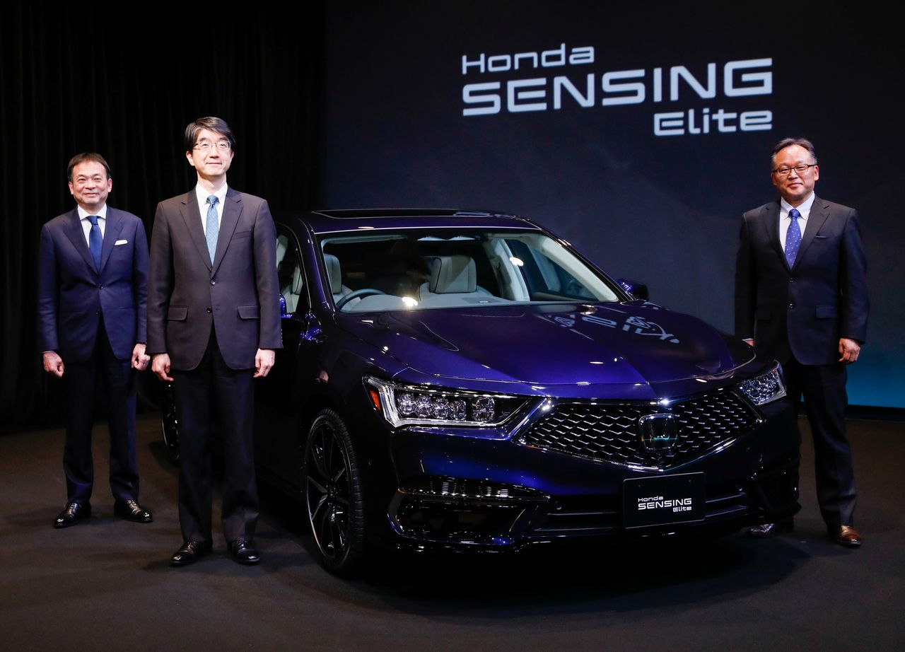 Yoichi Sugimoto, Executive Chief Engineer at the Advanced Technology Research Institute of the Honda Research Institute, and other executives pose next to the company's all-new Legend sedan, equipped with level 3 autonomous driving technology, during an unveiling in Tokyo, Japan March 4, 2021. REUTERS/Issei Kato