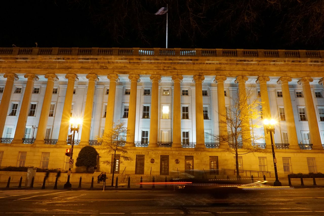 FILE PHOTO: A vehicle drives past the U.S. Treasury Department in Washington, D.C., U.S. December 13, 2020. Picture taken with a long exposure. REUTERS/Raphael Satter