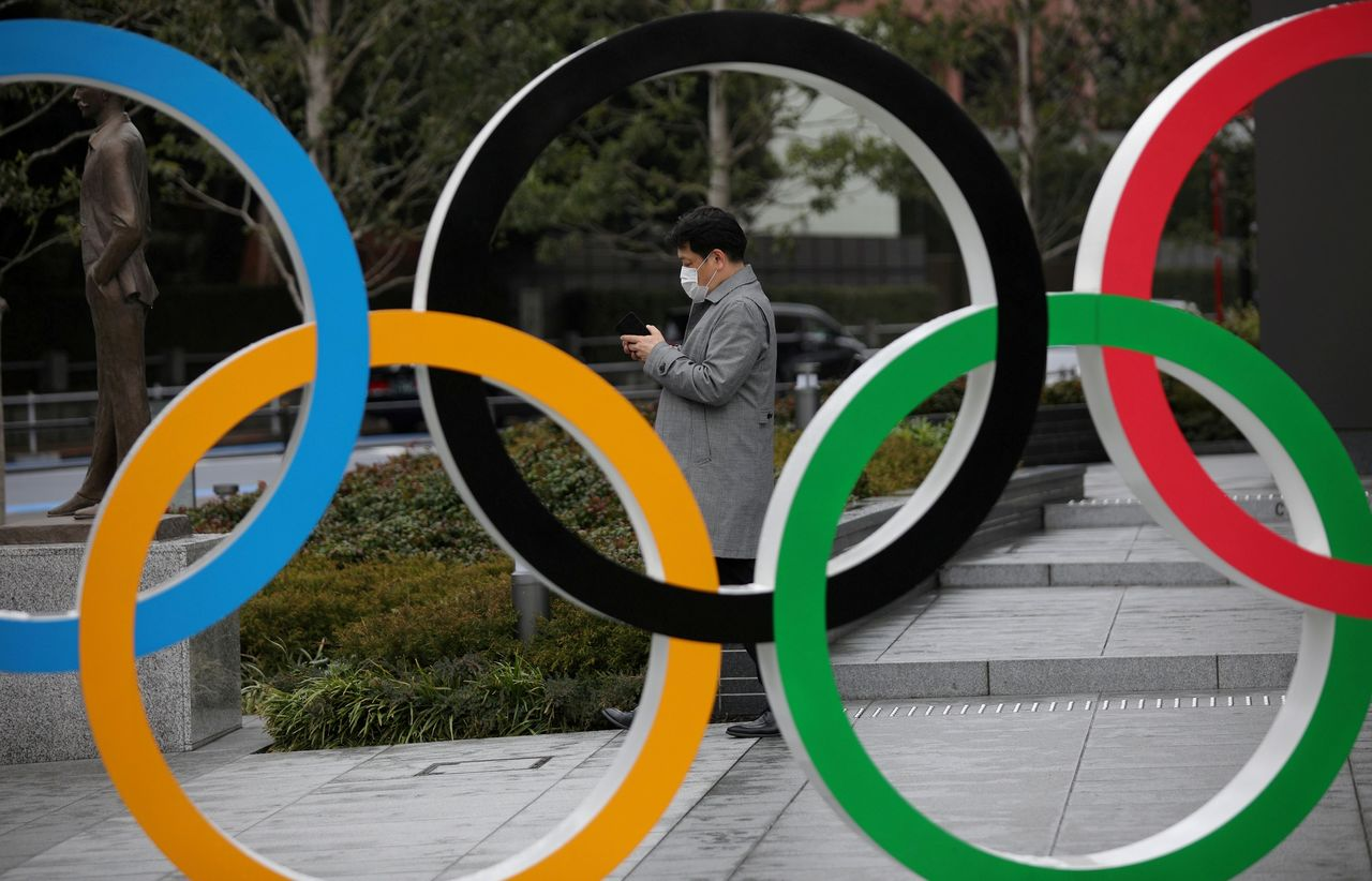 FILE PHOTO: A man looks at his mobile phone next to The Olympic rings in front of the Japan Olympics Museum in Tokyo, Japan, March 4, 2020. REUTERS/Stoyan Nenov