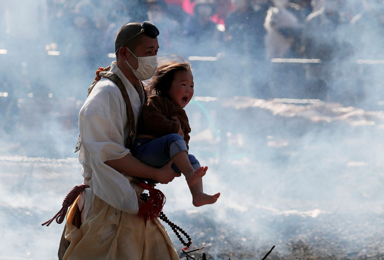 A Buddhist monk wearing a protective mask, amid the coronavirus disease (COVID-19) outbreak, carries a child as he walks across smoldering hot ground at the fire-walking festival, called hiwatari matsuri in Japanese, at Mt.Takao in Tokyo, Japan, March 14, 2021. REUTERS/Kim Kyung-Hoon