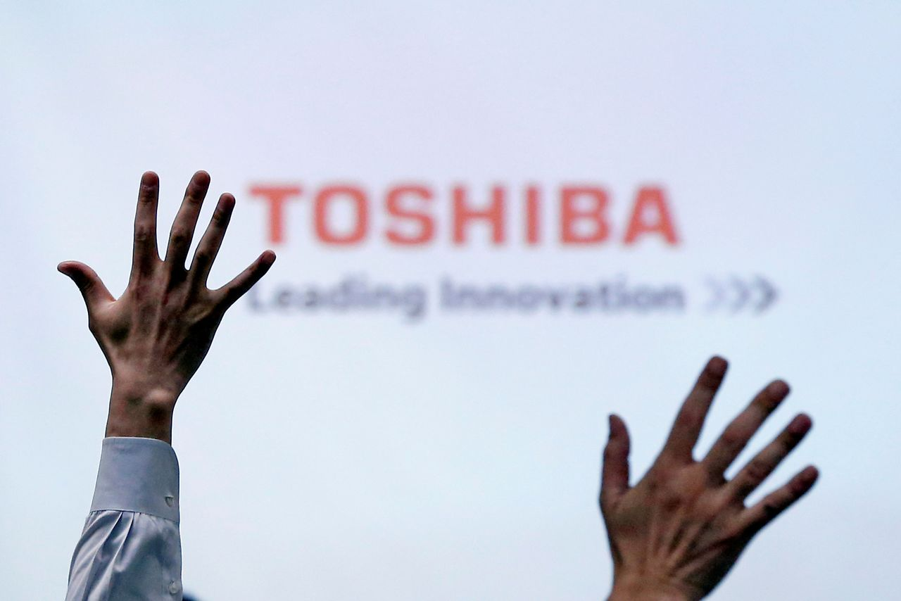 FILE PHOTO: Reporters raise their hands during a Toshiba news conference at the company's headquarters in Tokyo, Japan June 23, 2017. REUTERS/Issei Kato/File Photo
