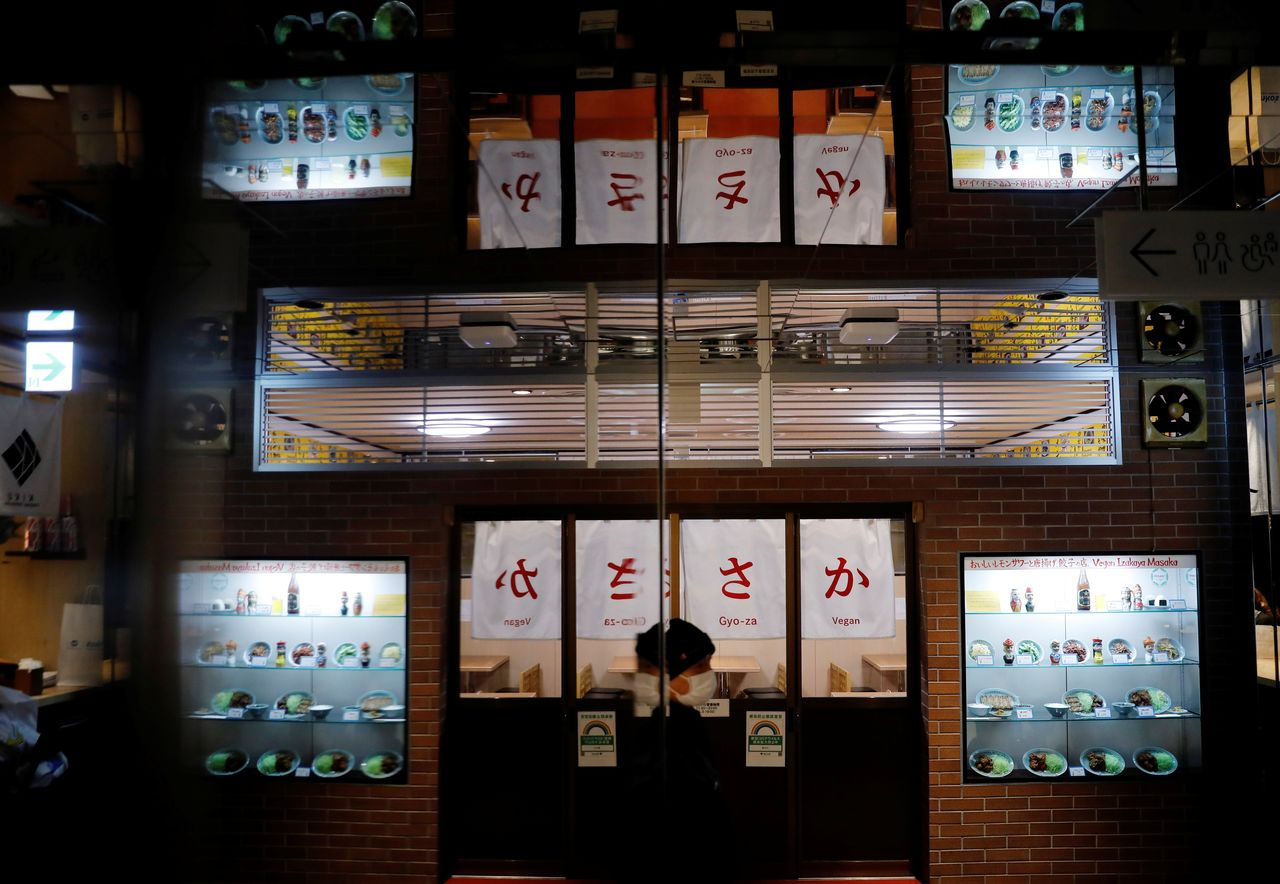 A man wearing a protective mask walks past vegan izakaya restaurant Masaka which has no guests during the dinner hour in Tokyo, Japan, March 2, 2021. REUTERS/Kim Kyung-Hoon