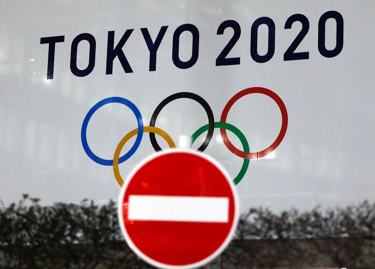 FILE PHOTO: The logo of Tokyo 2020 Olympic Games that have been postponed to 2021 due to the coronavirus disease (COVID-19) outbreak, is seen through a traffic sign at Tokyo Metropolitan Government Office building in Tokyo, Japan January 22, 2021. REUTERS/Issei Kato
