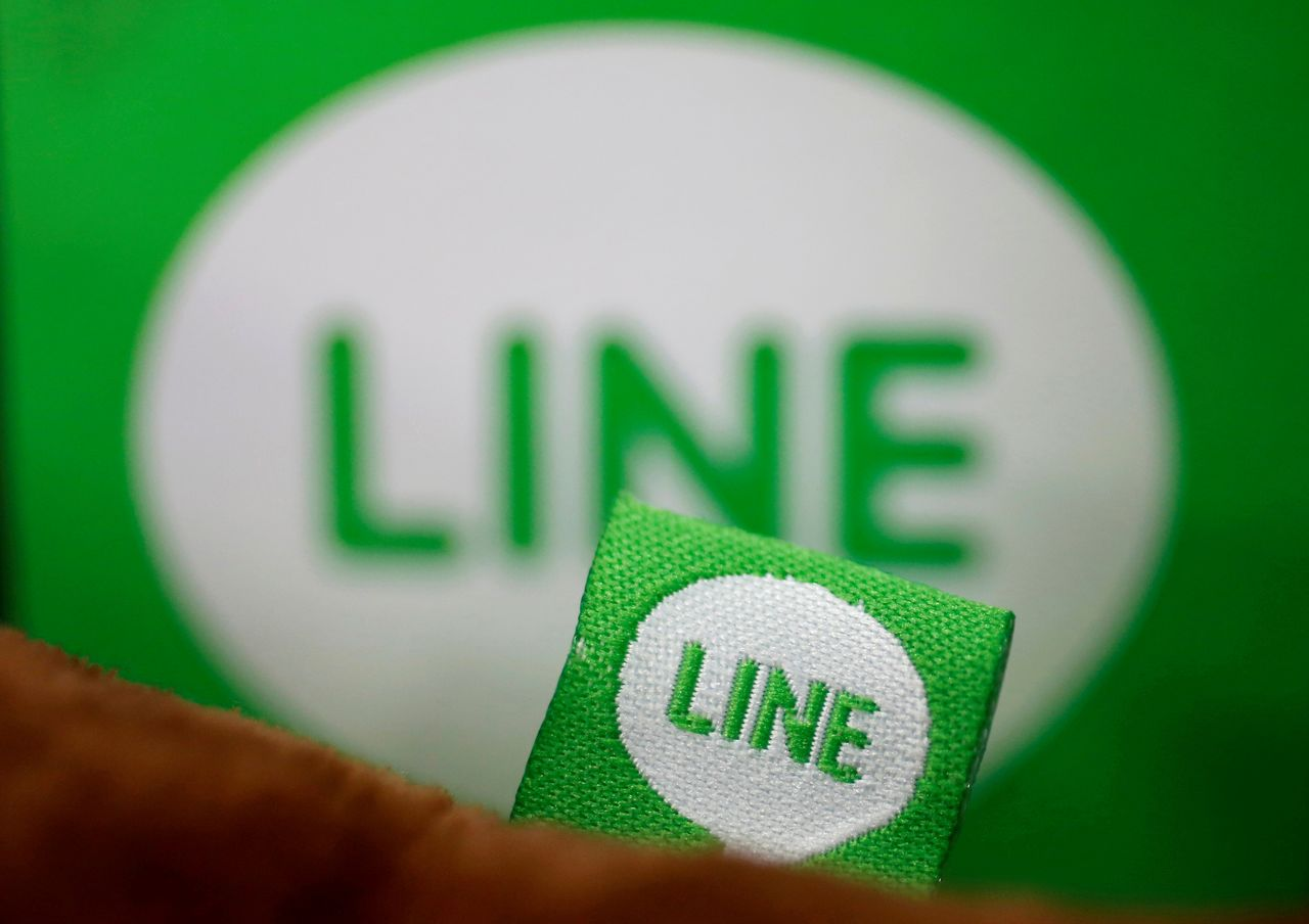 FILE PHOTO: The logo of free messaging app Line is pictured on a smartphone and the company's stuffed toy in this photo illustration taken in Tokyo, Japan, Sept. 23, 2014. REUTERS/Toru Hanai/Illustration