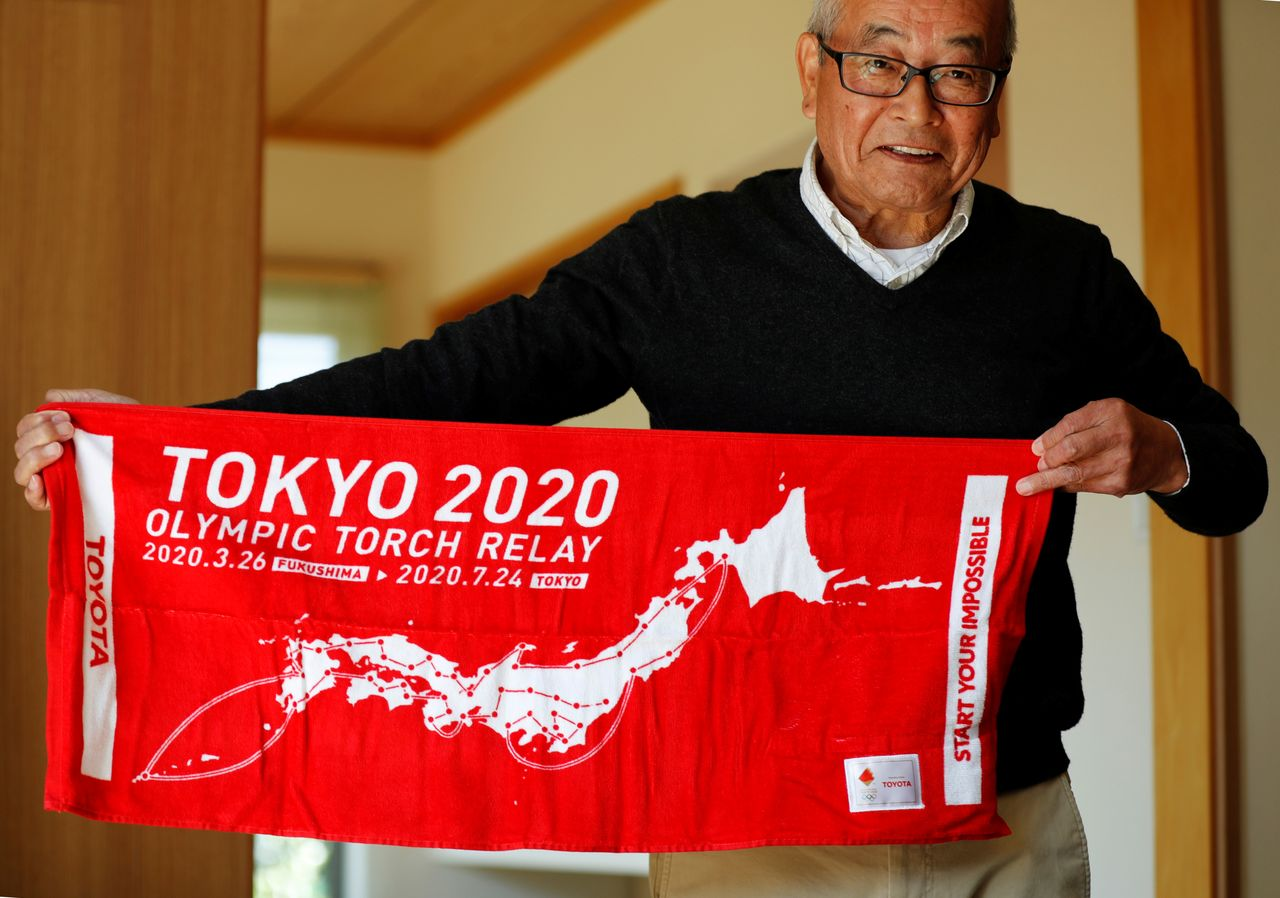 Masao Hashimoto who is going to run as a torch bearer on the first day of the torch relay at the Tokyo 2020 Olympic Games shows a towel promoting the torch relay during an interview with Reuters in Iwaki, Fukushima prefecture, Japan, March 24, 2021. REUTERS/Kim Kyung-Hoon