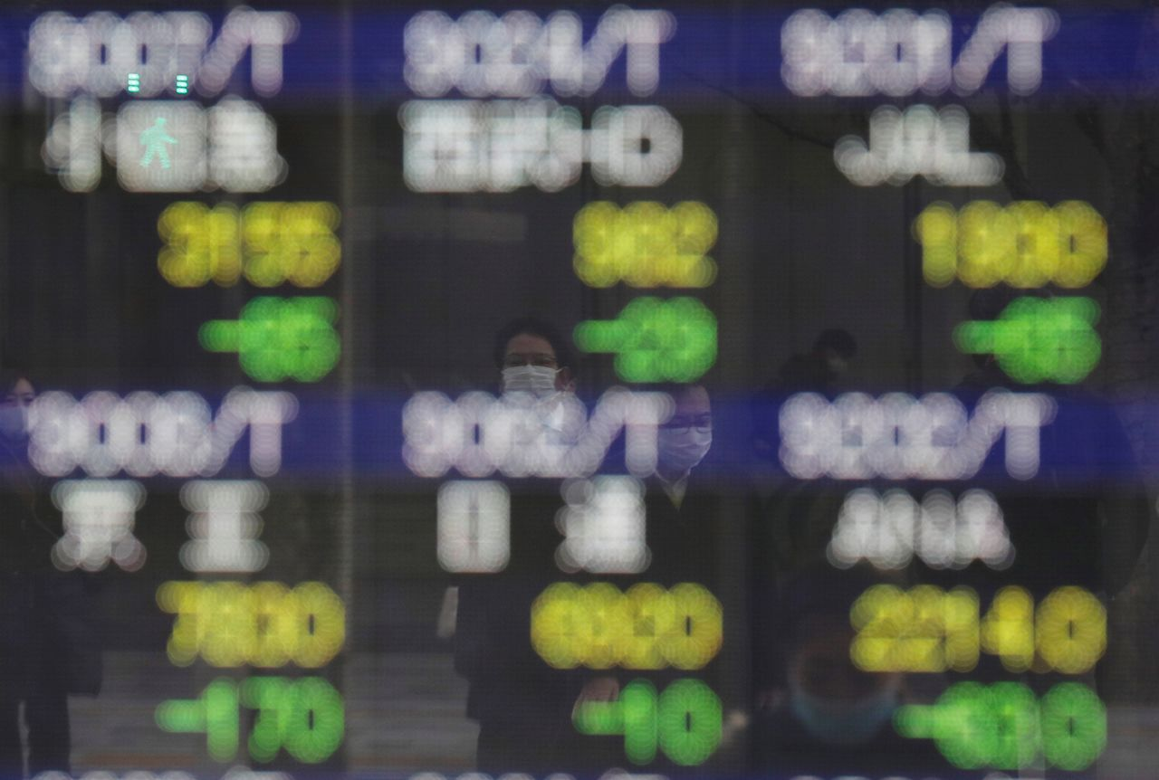 FILE PHOTO: Pedestrians wearing facial masks, following the coronavirus disease (COVID-19) outbreak, are reflected on an electric board showing stock prices outside a brokerage at a business district in Tokyo, Japan, January 4, 2021. REUTERS/Kim Kyung-Hoon