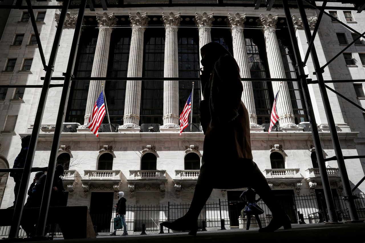 FILE PHOTO: People are seen outside the New York Stock Exchange (NYSE) in New York City, U.S., March 19, 2021. REUTERS/Brendan McDermid/File Photo