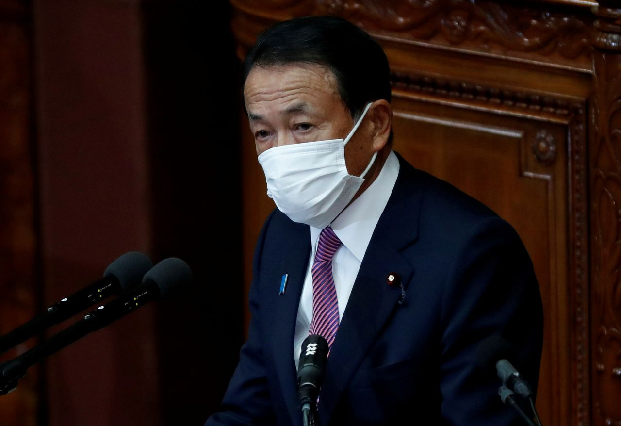 FILE PHOTO: Japan's Deputy Prime Minister and Finance Minister Taro Aso, wearing a protective face mask, delivers his policy speech at the opening of an ordinary session of the parliament in Tokyo, Japan January 18, 2021. REUTERS/Issei Kato/File Photo