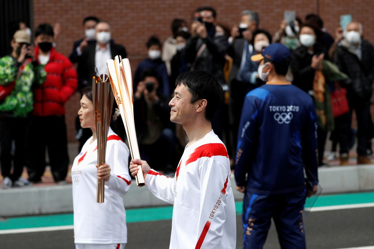 FILE PHOTO: Torchbearer Junko Ito hands the torch to the next torchbearer Yoshikazu Nishikata during the Tokyo 2020 Olympic torch relay on the second day of the relay in Fukushima, Japan March 26, 2021. REUTERS/Issei Kato