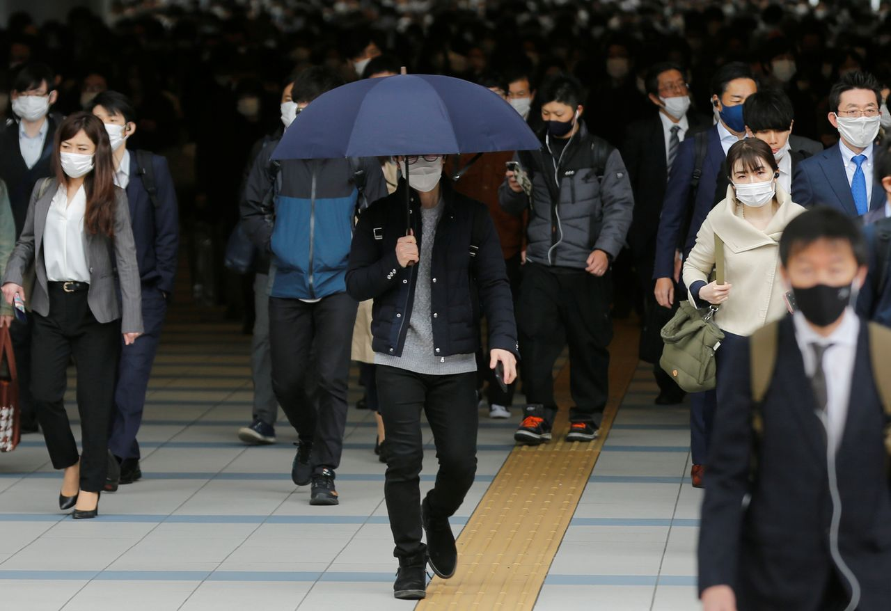 FILE PHOTO: A man walks with an umbrella on a sunny day as commuters wear protective face masks amid the coronavirus disease (COVID-19) pandemic in Tokyo, Japan, April 6, 2021. REUTERS/Kim Kyung-Hoon