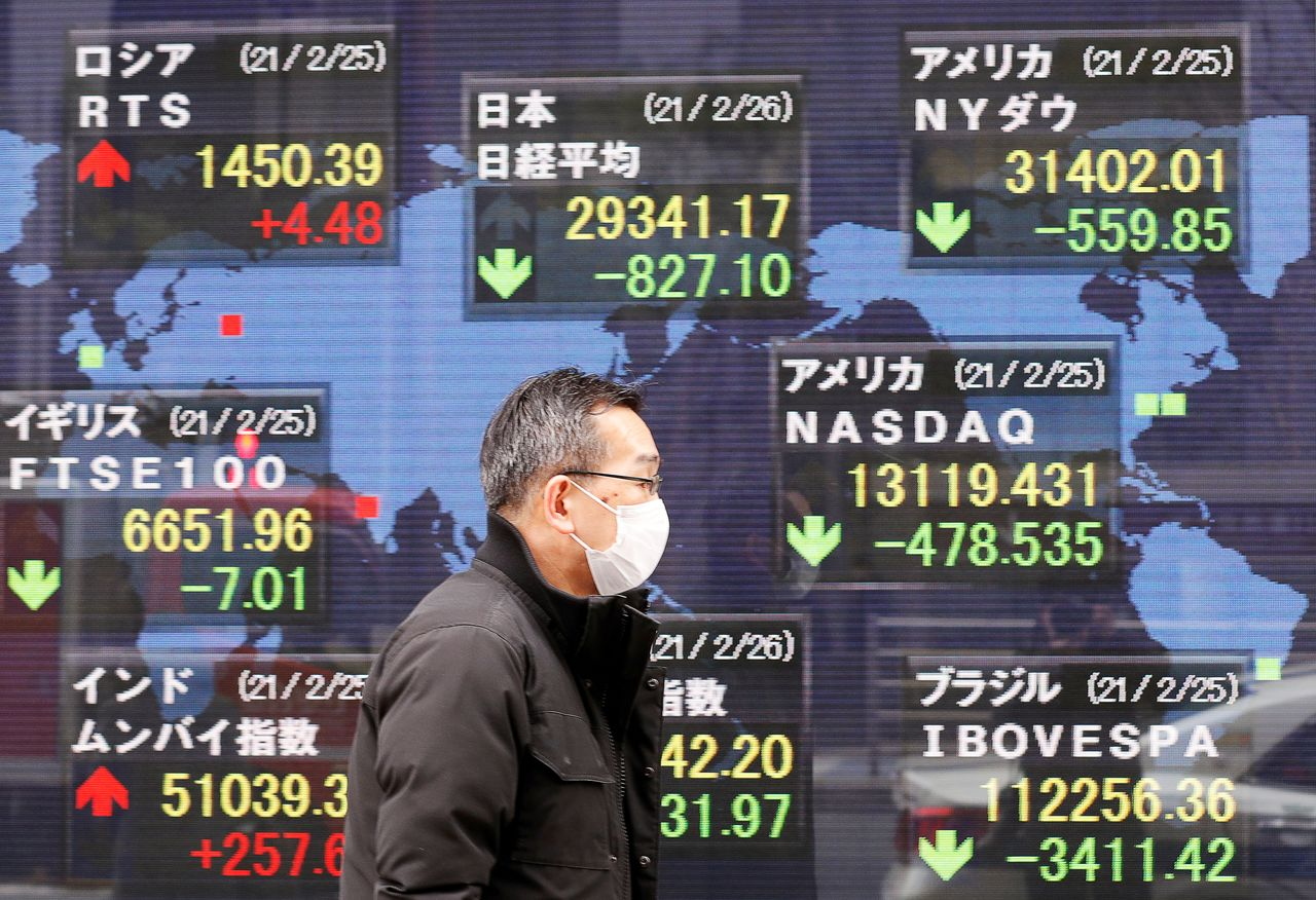 FILE PHOTO: A man walks past a stock quotation board at a brokerage in Tokyo, Japan February 26, 2021. REUTERS/Kim Kyung-Hoon/File Photo