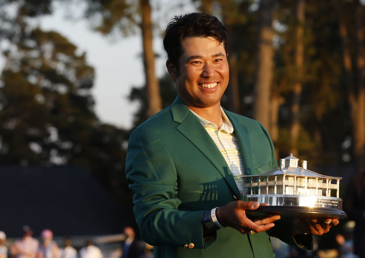 Golf - The Masters - Augusta National Golf Club - Augusta, Georgia, U.S. - April 11, 2021 Japan's Hideki Matsuyama celebrates with the green jacket and the trophy after winning The Masters REUTERS/Mike Segar