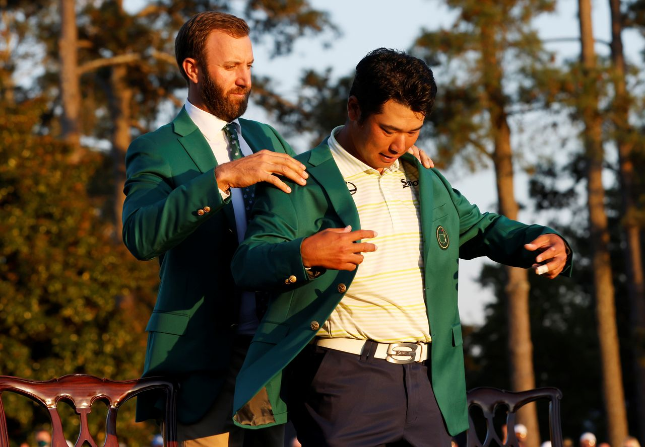 Golf - The Masters - Augusta National Golf Club - Augusta, Georgia, U.S. - April 11, 2021 Japan's Hideki Matsuyama has his green jacket put on by previous winner Dustin Johnson of the U.S. after winning The Masters REUTERS/Mike Segar