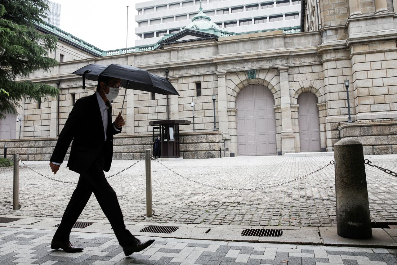 FILE PHOTO: A man wearing a protective mask walks past the headquarters of Bank of Japan amid the coronavirus disease (COVID-19) outbreak in Tokyo, Japan, May 22, 2020.REUTERS/Kim Kyung-Hoon/File Photo