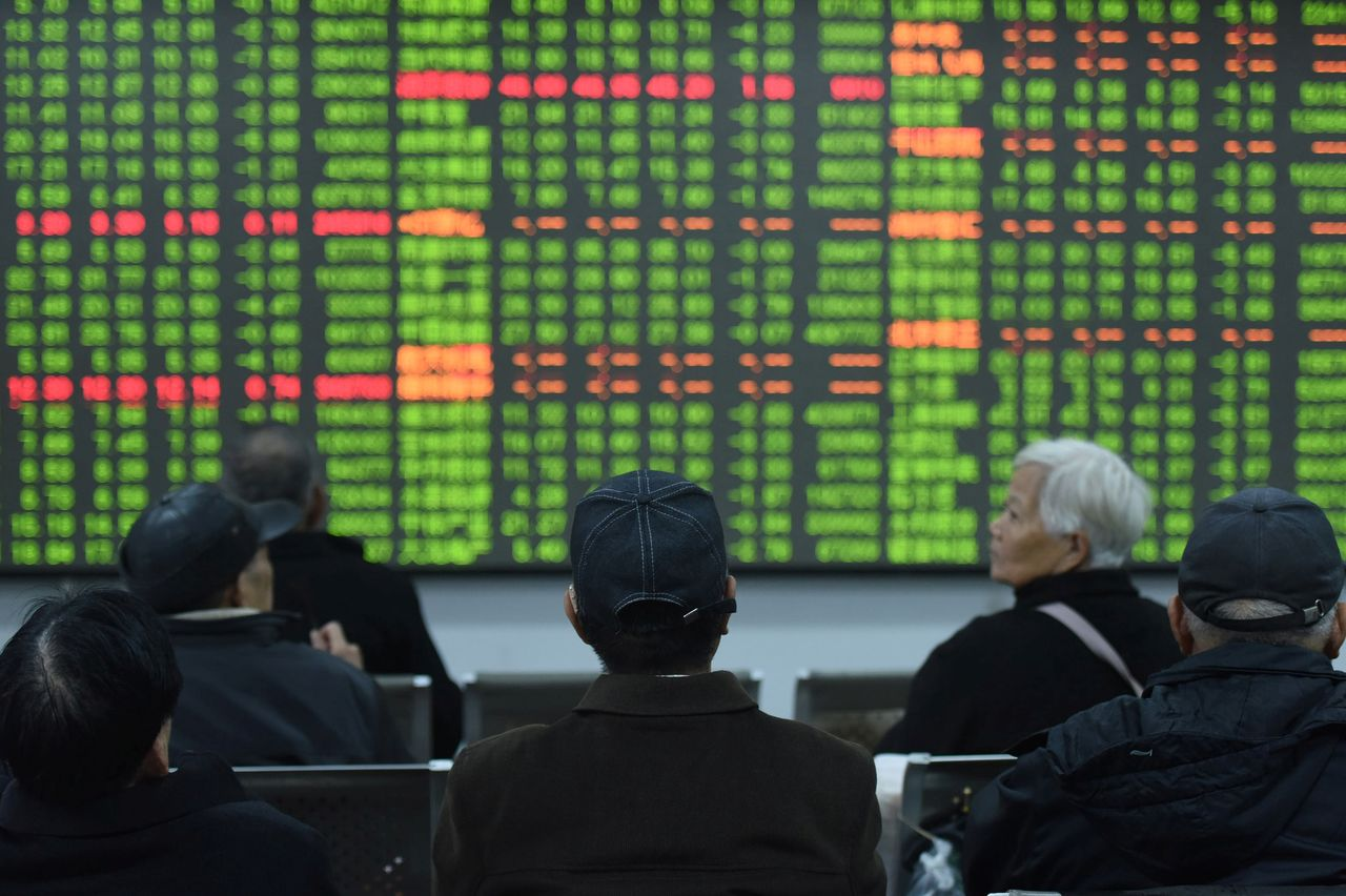 FILE PHOTO: Investors sit in front of a board showing stock information at a brokerage house on the first day of trade in China since the Lunar New Year, in Hangzhou, Zhejiang province, China February 3, 2020. China Daily via REUTERS