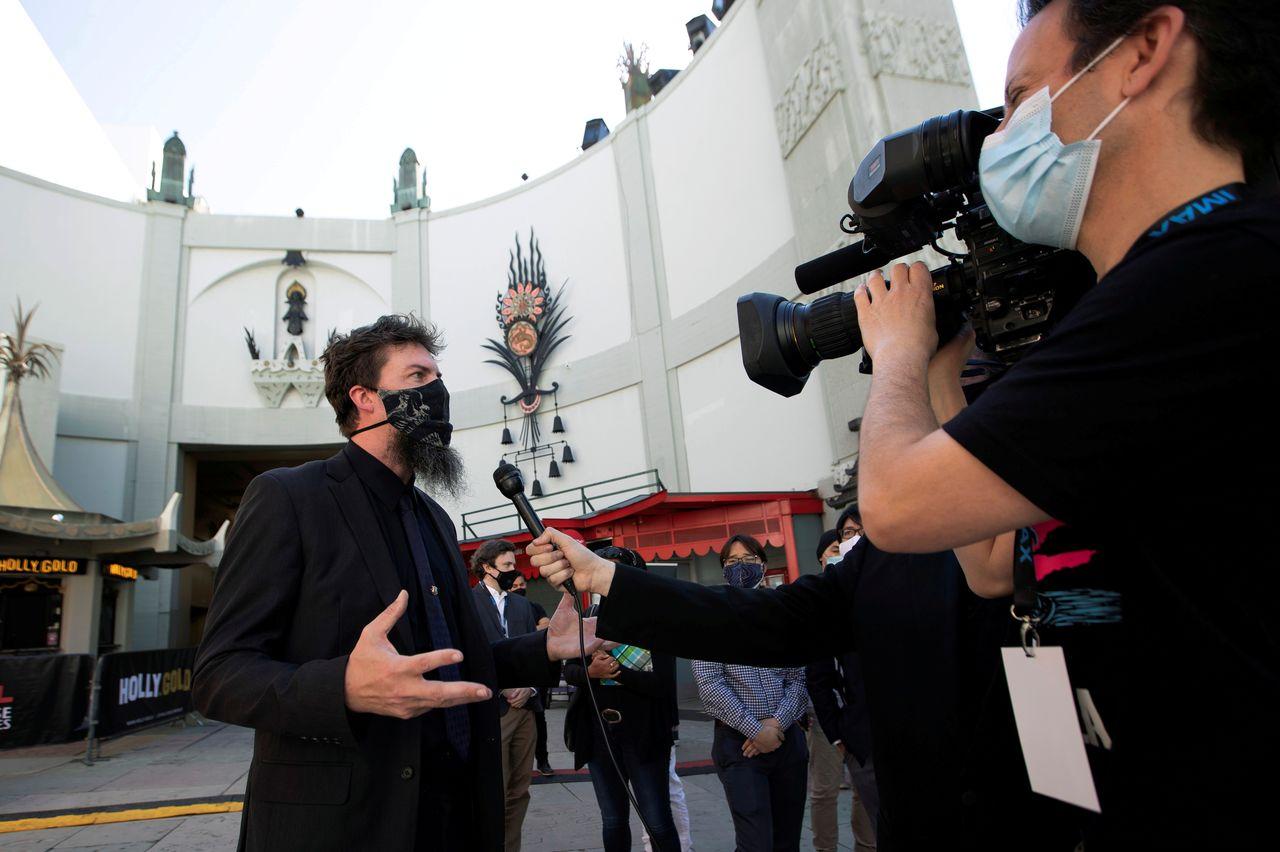 "FILE PHOTO: Adam Wingard, director of the upcoming movie ""Godzilla vs. Kong"", is interviewed at a ribbon cutting ceremony ahead of the reopening of the TCL Chinese theatre during the outbreak of the coronavirus disease (COVID-19), in Los Angeles, California, U.S., March 29, 2021.  REUTERS/Mario Anzuoni/File Photo"
