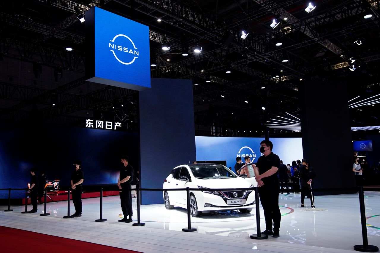 Staff members stand near a Nissan Leaf electric vehicle (EV) displayed at the Nissan booth during a media day for the Auto Shanghai show in Shanghai, China April 19, 2021. REUTERS/Aly Song