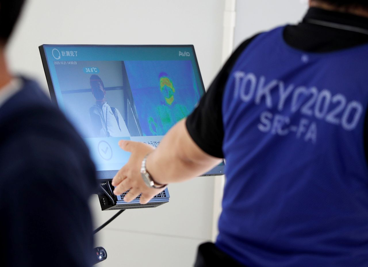 FILE PHOTO: A screen displays body temperature check results during a test for games spectators, hosted by Tokyo Organising Committee of the Olympic and Paralympic Games, ahead of the summer games that have been postponed to 2021 due to the coronavirus disease outbreak, at Tokyo Big Sight, Japan October 21, 2020. REUTERS/Issei Kato