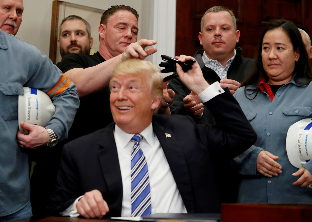 FILE PHOTO: U.S. President Donald Trump gives out pens he used to sign presidential proclamations placing tariffs on steel and aluminum imports to workers from the steel and aluminum industries at the White House in Washington, U.S. March 8, 2018. REUTERS/Leah Millis