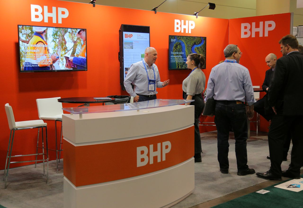 FILE PHOTO: Visitors to the BHP (formerly known as BHP Billiton) booth speak with representatives during the Prospectors and Developers Association of Canada (PDAC) annual convention in Toronto, Ontario, Canada March 4, 2019. REUTERS/Chris Helgren