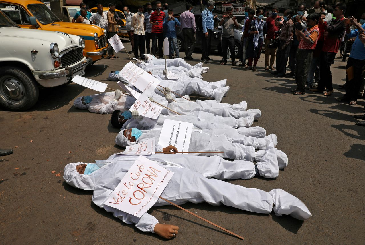 FILE PHOTO: Demonstrators in protective suits and masks lie on a road during a protest demanding to stop election and campaign rallies in the eastern state of West Bengal, amidst the spread of the coronavirus disease (COVID-19), near the office of the Election Commission in Kolkata, India, April 7, 2021. REUTERS/Rupak De Chowdhuri