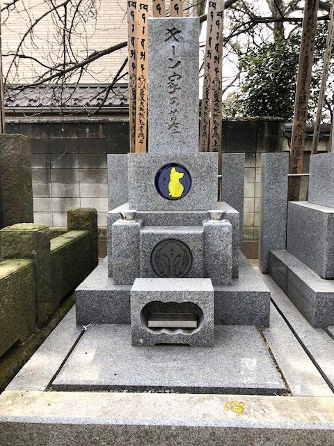 Keene's family grave, prepared by himself before his death at a temple near his home. As he was born in the year of the dog, he chose a yellow dog as his family crest. It is also a play on words (kiinu) on his surname.
