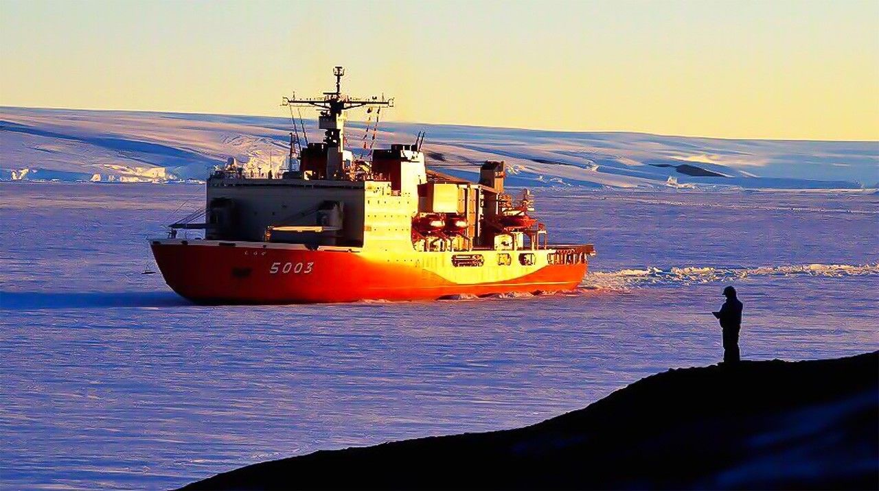 The icebreaker Shirase approaches the Japanese research base on East Ongul Island against the dramatic backdrop of the Antarctic land mass.