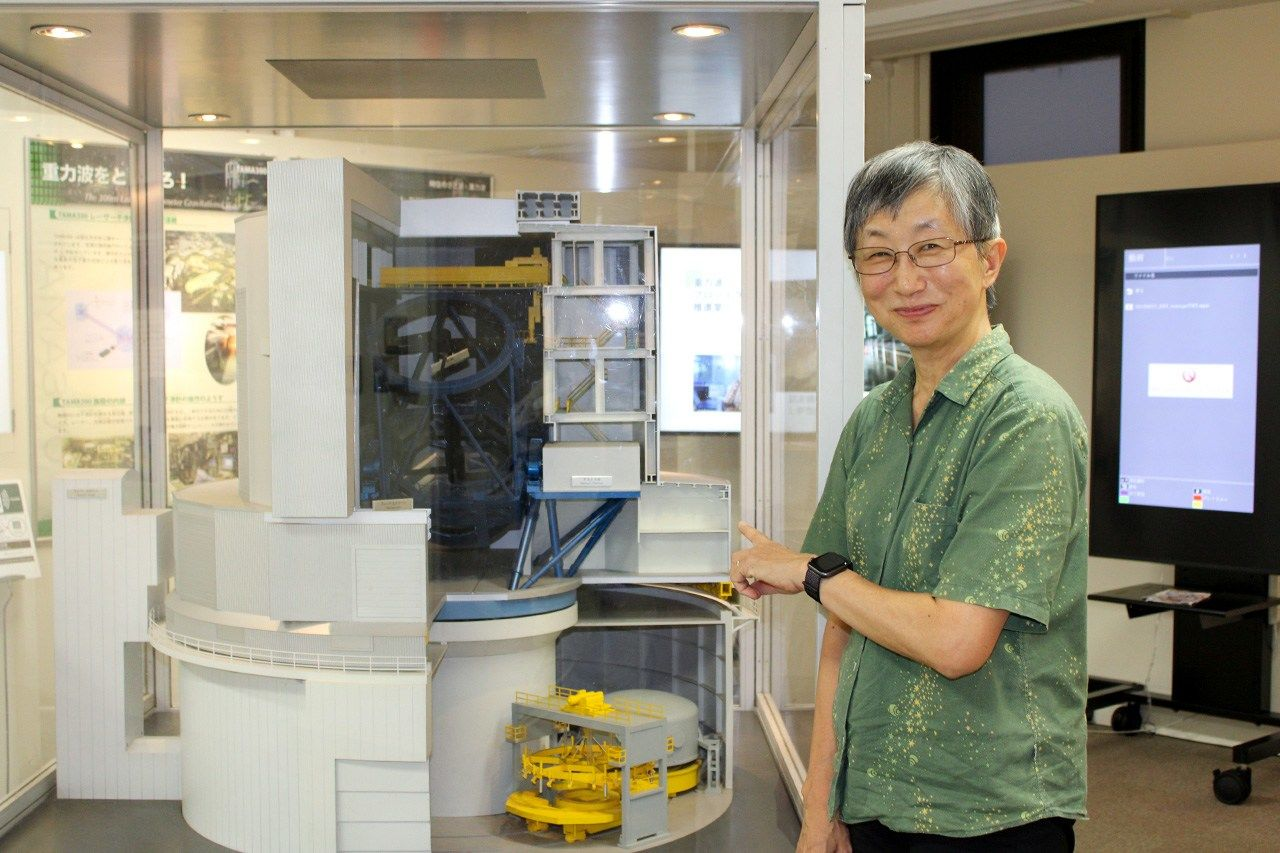 Hayashi beside a model of the Subaru Telescope on exhibit at the National Astronomical Observatory's headquarters in Mitaka, Tokyo. (© Nippon.com)
