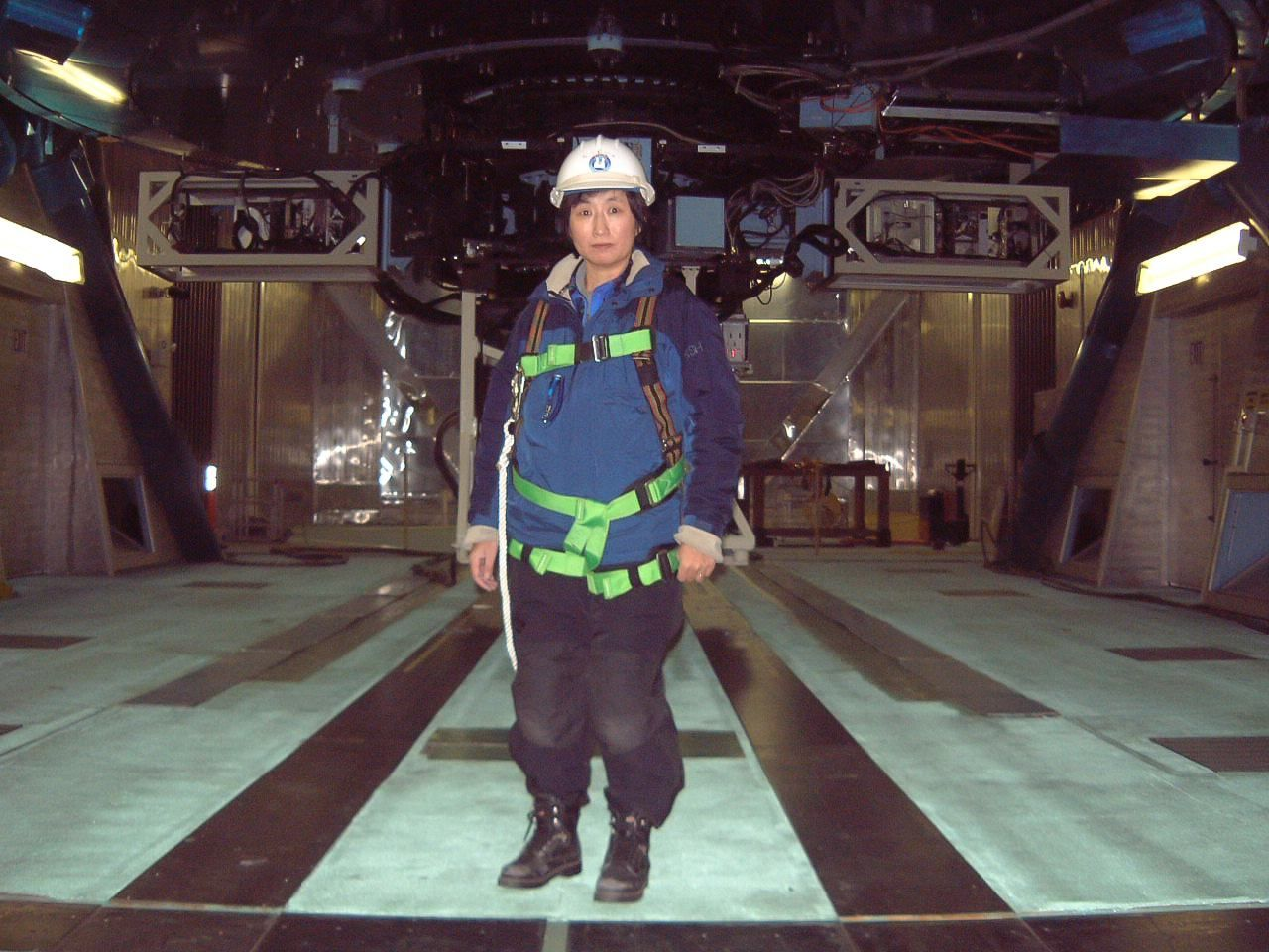 Hayashi Saeko in 2002, photographed in front of the Subaru Telescope. She is wearing a safety harness necessary to operate an aerial lift for the direct inspection of the primary mirror. (Photo courtesy of Hayashi Saeko)