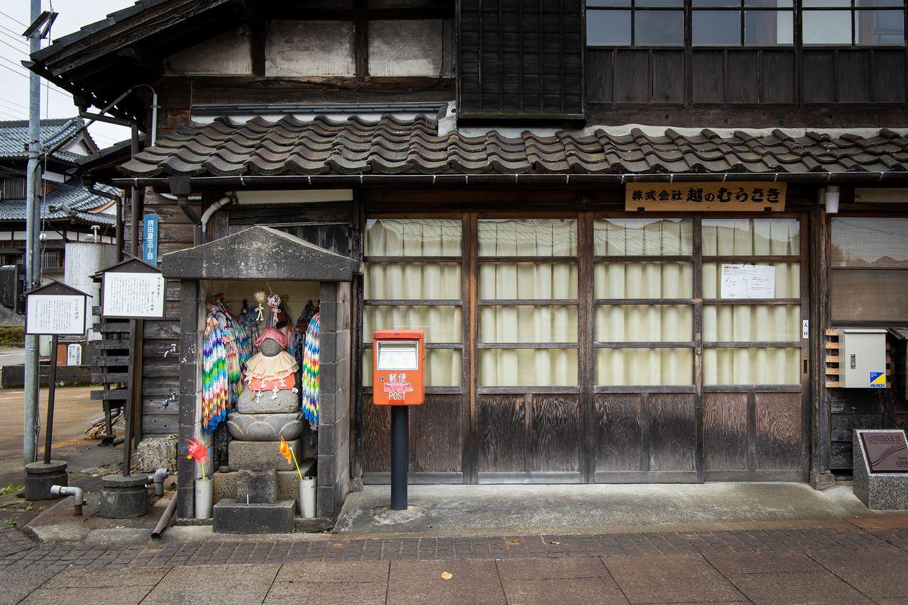 """Una estatua de bodhisattva Jizō frente a la sede de Koshi no Murasaki sirve como una señalización del camino de Mikuni. En la base están grabadas las direcciones """"hacia Edo, a la derecha; hacia Yamaji, a la izquierda""""."""